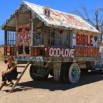 Amie sitting on salvation mountain truck
